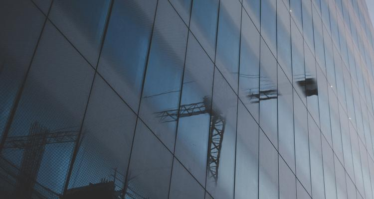 Reflection of crane in glass building